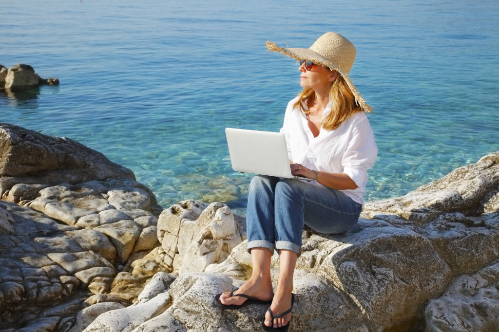 Portrait of beautiful business woman sitting by the sea and working online with her laptop. Middle age female wearing straw hat and sunglasses.
